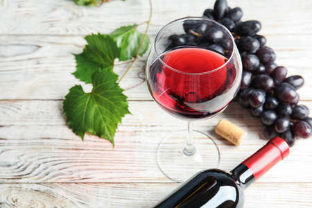 Glass and bottle of red wine with fresh ripe juicy grapes on table