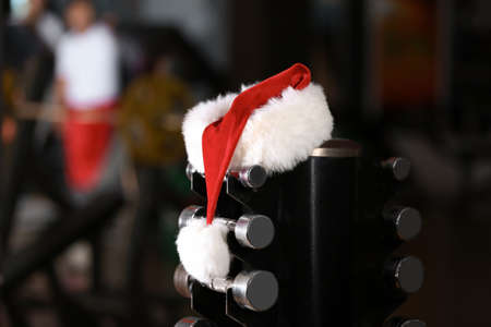 Santa Claus hat on stand with dumbbells in gym