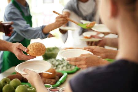 Freiwillige, die drinnen Essen für arme Leute servieren