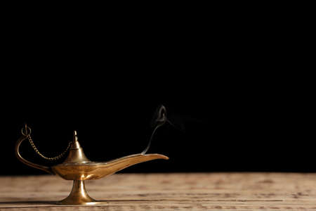 Aladdin lamp of wishes on wooden table against black background Stock Photo