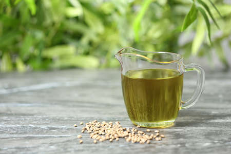 Glass pitcher with hemp oil on grey table against blurred background