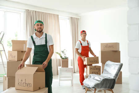Male movers with boxes in new house Banque d'images
