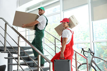 Male movers carrying boxes in new house Foto de archivo