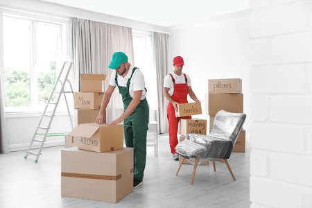 Male movers with boxes in new house Foto de archivo - 107871619