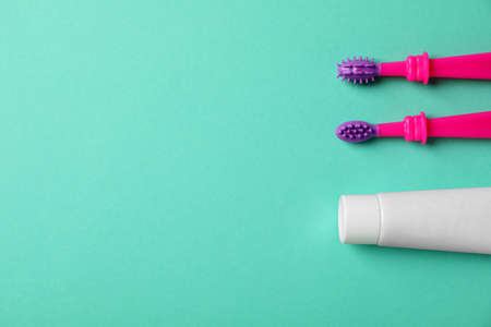 Baby toothbrushes and toothpaste with space for text on color background, top view Stock Photo