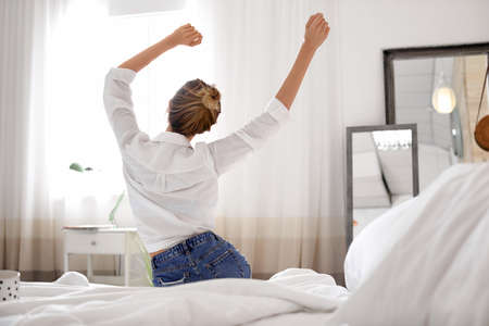 Young happy woman stretching on bed at home. Lazy morning