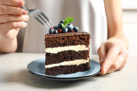 Woman with slice of chocolate sponge berry cake at table, closeup Standard-Bild