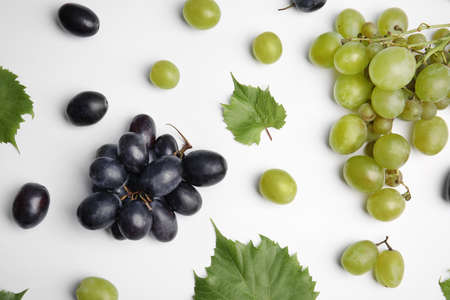 Fresh ripe juicy grapes and leaves on white background, top view Stockfoto