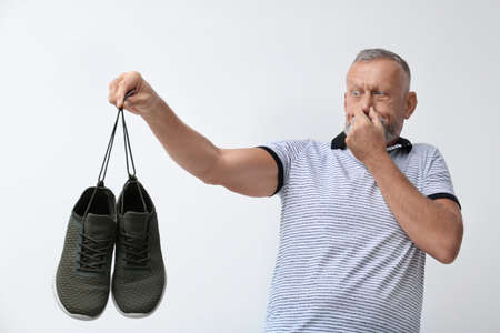 Man feeling bad smell from shoes on white background. Air freshener 스톡 콘텐츠