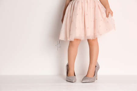Little girl in oversized shoes near white wall with space for text, closeup on legs Banco de Imagens