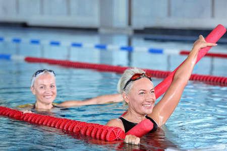 Sportive senior women doing exercises in indoor swimming pool Standard-Bild - 107752300