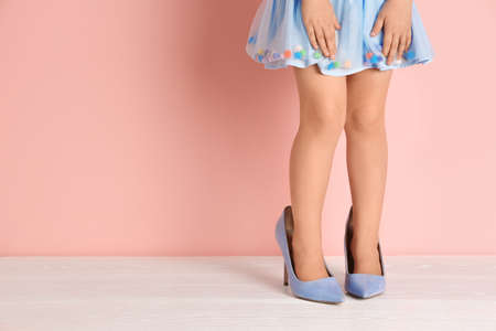 Little girl in oversized shoes near color wall with space for text, closeup on legs Foto de archivo - 107423044