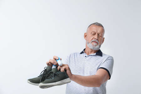 Man putting capsule shoe freshener in footwear on white background. Space for text