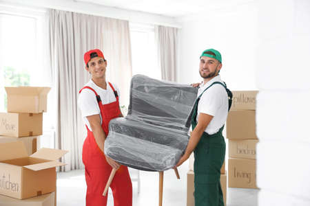 Male movers carrying armchair in new house