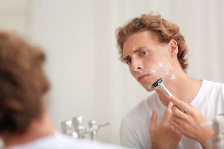 Junger hübscher Mann, der sich im Badezimmer rasiert Standard-Bild