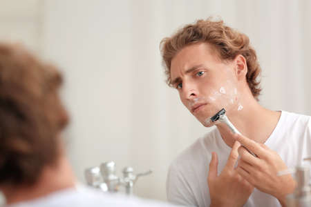 Young handsome man shaving in bathroom