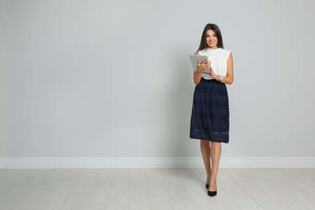 Beautiful woman with tablet wearing office clothes against gray wall. Space for text