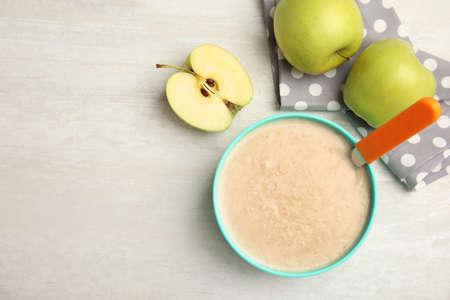 Composición plana con plato de comida saludable para bebés y espacio para texto sobre fondo claro