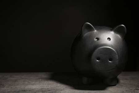 Black piggy bank on table against dark background with space for text. Poverty concept