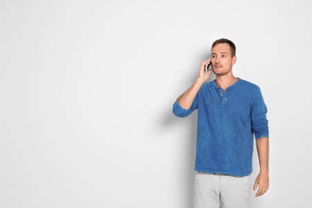 Young man talking on phone against white background. Space for text