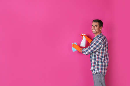 Man in gloves cleaning color wall with rag