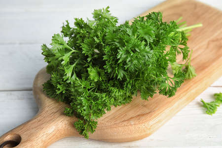 Wooden board with fresh green parsley on table