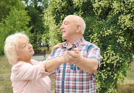 Cute elderly couple in love dancing outdoors