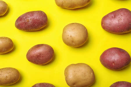 Flat lay composition with fresh organic potatoes on color background