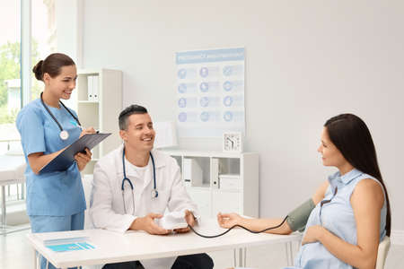 Doctor and his assistant checking pregnant woman's blood pressure in hospital. Patient consultation Stock Photo