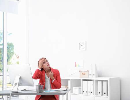 Young woman suffering from heat under broken air conditioner in office Foto de archivo