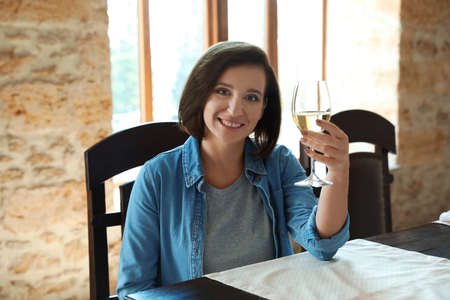 Woman with glass of white wine at table indoors Imagens
