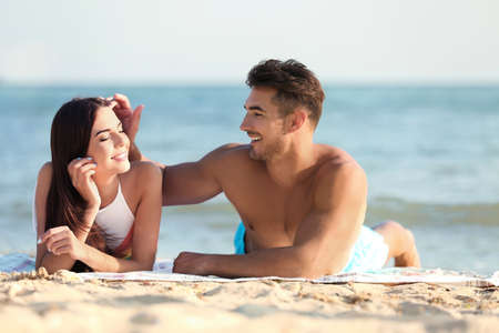 Happy young couple lying together on beach