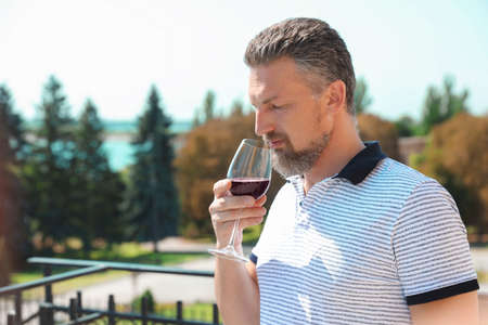 Man with glass of red wine outdoors