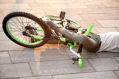 Little boy fallen off his bicycle on street, closeup Archivio Fotografico