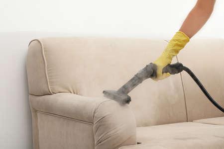 Bidello che rimuove lo sporco dal divano con pulitore a vapore, primo piano