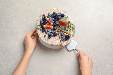 Woman and delicious homemade cake with fresh berries on table, top view