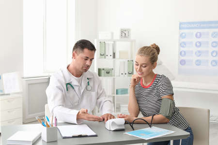 Doctor checking patients blood pressure at table in office Stock Photo