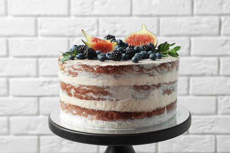 Delicious homemade cake with fresh berries on stand near brick wall