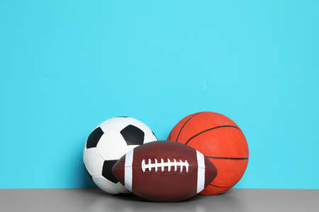 Different sport balls on table against color background. Space for text 写真素材
