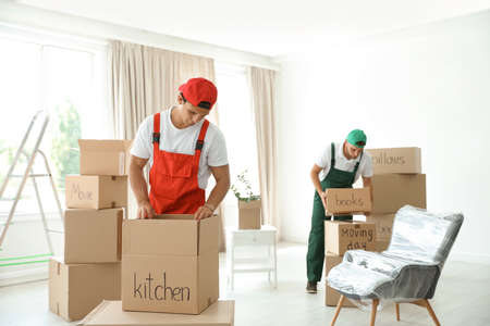 Male movers with boxes in new house Foto de archivo