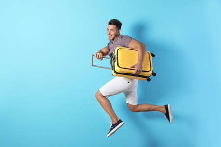 Young man jumping with suitcase on color background