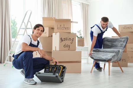 Mudanzas masculinas con instrumentos y sillón en casa nueva Foto de archivo