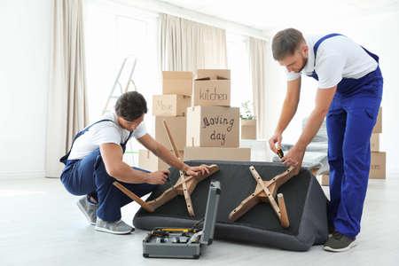 Mâle déménageurs assemblage canapé dans une nouvelle maison