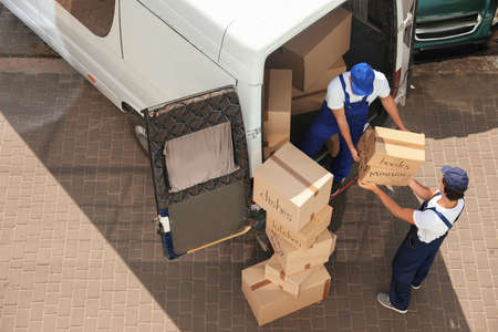 Mannelijke verhuizers lossen dozen uit busje buitenshuis, boven weergave Stockfoto - 107874990