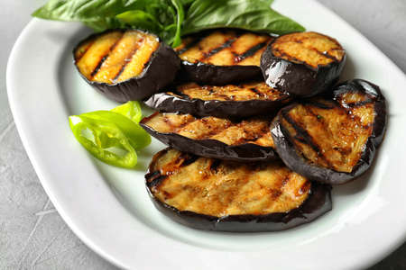 Plate with fried eggplant slices on table, closeup