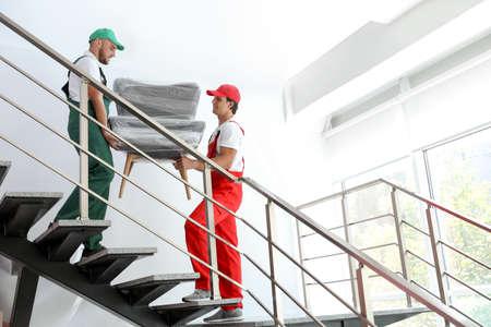 Mâle déménageurs transportant un fauteuil dans une nouvelle maison
