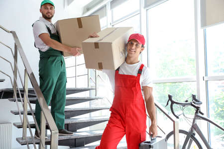 Male movers carrying boxes in new house Banque d'images