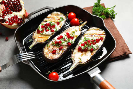 Grill pan with fried eggplants on table