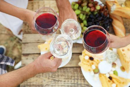 Vrienden houden van glazen wijn boven picknicktafel op wijngaard, bovenaanzicht