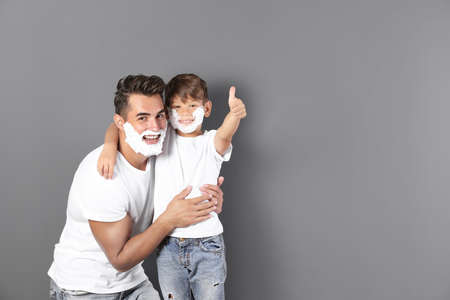 Father and son with shaving foam on faces against color background. Space for text Stock Photo